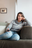 Young woman watching tv home sofa Royalty Free Stock Photography