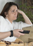 Young woman watching TV. With remote in hands Stock Photos
