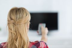 Young woman watching tv in room Stock Photos