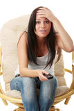 Young woman watching TV - scared. Young woman watching TV with remote control in hand while sitting on armchair - surprised or scared ,isolated - view from TV Royalty Free Stock Photo