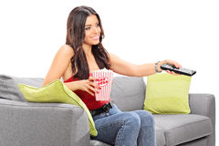 Young woman watching TV seated on a sofa. And holding a box of popcorn isolated on white background Royalty Free Stock Photos