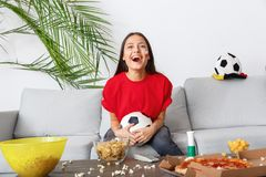 Young woman sport fan watching match in a red t-shirt cheering royalty free stock images
