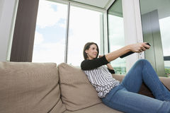 Young woman watching TV on sofa at home Stock Photo