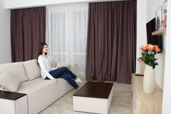 Young woman watching tv on sofa in living room using remote control Royalty Free Stock Photo