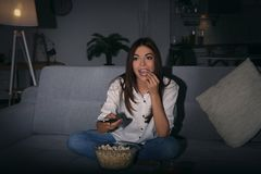 Young woman watching TV on sofa. At night Stock Photo