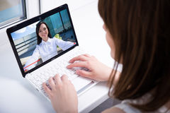 Young woman watching video blog on laptop. Young women watching video blog on laptop at home Stock Photography