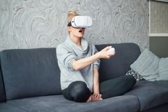 Young woman watching videos or playing with VR glasses on head royalty free stock photography