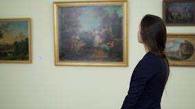 Young woman watching works of art paintings on the exhibition at city art gallery. Elegant girl looks at the pictures in. The museum of modern art. Paintings in stock footage