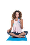 Young woman with water bottle sitting on exercise mat Royalty Free Stock Photography