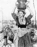 Young woman with water bucket on her head next to a well Stock Photos
