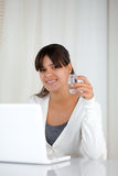 Young woman with a water glass in front of laptop Stock Photography