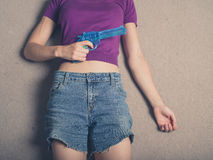 Young woman with water pistol on carpet Royalty Free Stock Photos