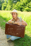 Young woman with water and suitcase on grass Royalty Free Stock Images