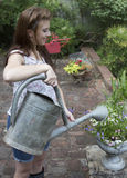 Young woman with watering can Royalty Free Stock Image