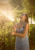 Young woman watering garden with hose pipe Stock Images