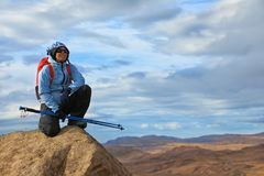 Young woman sits on the top of cliff Stock Photography