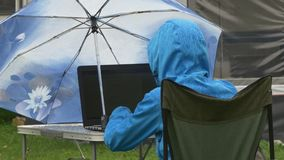 A young woman in waterproof clothing works on laptop under rain stock video