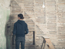 Young woman by wattle and daub wall. A young woman is standing by a wattle and daub wall Stock Photos