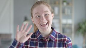 Young woman waving at the camera stock video footage