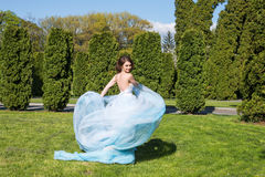 Young woman in waving dress in the park Royalty Free Stock Image