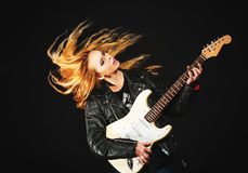 Young woman with waving hair play electric guitar Royalty Free Stock Photography