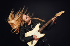 Young woman with waving hair play electric guitar Stock Images