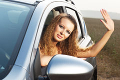 Young woman waving hand. Young woman looking out of car and waving hand Royalty Free Stock Images