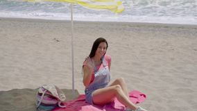 Young woman waving hand while on beach blanket. Cute young woman waving hand while on pink beach blanket in sand under shade with bag and sandals stock footage