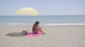 Young woman waving hand while on beach blanket. Cute young woman waving hand while on pink beach blanket in sand under shade with bag and sandals stock video footage