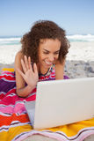 Young woman waving her hand in front of her laptop Royalty Free Stock Photo