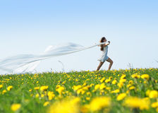 A young woman waving a silk blanket in the field Royalty Free Stock Photography
