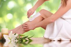Young woman waxing her legs Stock Photography