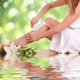 Young woman waxing her legs Stock Image