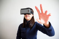 Young Woman wear reality device and hand want to touch some Royalty Free Stock Images