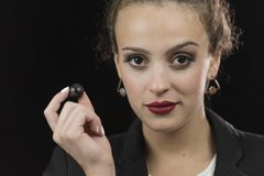 Young woman wear white shirt and jacket in studio black backgrou. Nd, with serious bun hair holding a fruit grape close to her mouth Stock Images