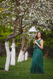 Young woman weared in long green dress in a blooming apple garden Royalty Free Stock Photos