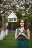 Young woman weared in long green dress in a blooming apple garden Stock Photo