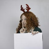 Young woman wearing antlers and holding empty sign Royalty Free Stock Image