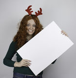 Young woman wearing antlers and holding empty sign Royalty Free Stock Photo