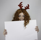 Young woman wearing antlers and holding empty sign Stock Photography