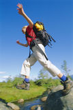 Young woman wearing backpack leaping across river Stock Image