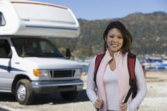 Young woman wearing backpack by RV at lake Royalty Free Stock Photo