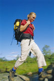 Young woman wearing backpack stepping across river Stock Photos
