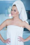 Young Woman Wearing Bath Towel with Hands on Hips. Confident Smirking Young Woman Wearing Bath Towel with Hands on Hips and Hair in Towel Stock Images