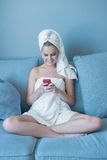 Young Woman Wearing Bath Towel with Red Cell Phone. Young Woman Wearing Bath Towel Looking Down at Red Cell Phone and Sitting on Blue Sofa Stock Photo