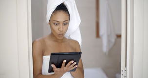 Young Woman Wearing Bath Towel Using Tablet Computer Royalty Free Stock Images