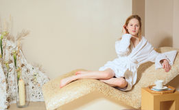 Young woman wearing a bathrobe sitting on the spa relax room Royalty Free Stock Image