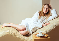 Young woman wearing a bathrobe sitting on the spa relax room Royalty Free Stock Images