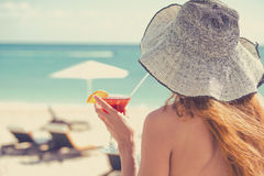 Young woman wearing a bikini holding a cocktail enjoying ocean view stock photography
