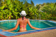 Young woman wearing bikini in small pool. Back view of the torso of slim beautiful woman in the small pool with tropical leaves on background Stock Photo